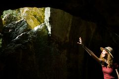 Young explorer a girl in hat pointing and hole in the ancient cave stock photo