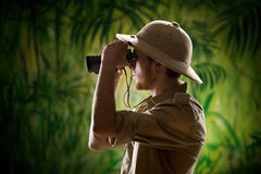 Young explorer looking through binoculars. Young confident explorer in the rainforest jungle looking through binoculars Stock Photos