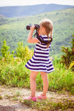 Young explorer looks at the scenic view through binoculars Royalty Free Stock Photography