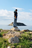 Young explorer. A young man standing on a rock with eyes on the horizon Royalty Free Stock Photo