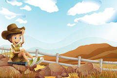 A young explorer sitting above the rock near the wooden fence Royalty Free Stock Photo