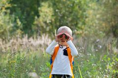 Free Young Explorer Watching With Binoculars Of Birds In The High Grass Stock Photos - 144057613
