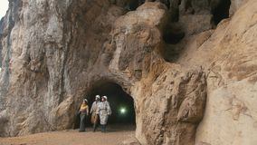 Young explorers in helmets coming out from the large dark cave. Telephoto shot stock video footage