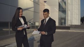 Business people while working near office building. Young expressive businessman scolds his assistant for mistakes in documents on outdoors against the backdrop stock video