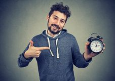 Young expressive happy hipster man holding alarm clock. And posing on gray background stock photography