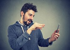 Man manipulating with smarpthone and gesturing. Young expressive man manipulating with gadget using magic and standing on gray background Royalty Free Stock Photo