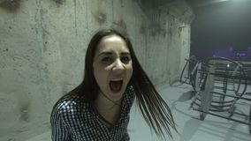 Woman posing in loft club. Young expressive woman screaming and posing among concrete walls of modern grungy club stock video footage