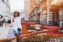 Black girl with retro cam on the street near flowerbed royalty free stock photo