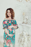 Young, extravagant, extraordinary pregnant girl, woman standing near the fireplace in the flowerpot snake modern dress. Young, extravagant, extraordinary Royalty Free Stock Images