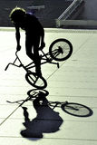 Young extreme bicycle rider. Young extreme rider on a grey urban concrete background Royalty Free Stock Photography