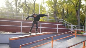 Young extreme skateboarder listening to the music in earphones grinding down rail in the skatepark. Slowmotion shot stock video footage
