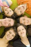 Young faces. Group of 6 teenagers lying on the floor head next to head. They're looking at camera and smiling Stock Photos