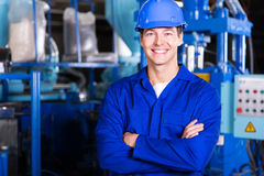 Young factory worker. Cheerful young factory worker with arms crossed stock photo