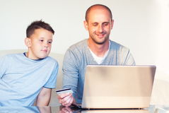 Young faher with child buying online at home Stock Image