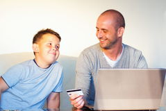 Young faher with child buying online at home Royalty Free Stock Photo