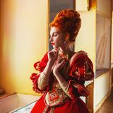 Young fairytale rococo queen portrait with historical hairstyle on light background. Renaissance princess with red hair. royalty free stock photography