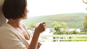 Young famale drinking water on the resort hotel  balcony. 