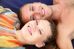 Young family. A young girl and her husband relax on the beach and smiling cheerfully Royalty Free Stock Image