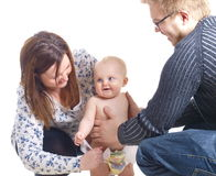 Young family. Young couple is dressing a baby boy Royalty Free Stock Image