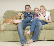 Young family. Sitiing on sofa and eating popcor Stock Photos