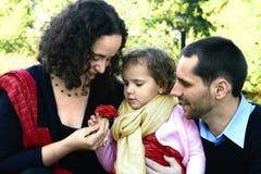 Young family admiring a rose Stock Photos