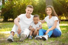 Young family with adopted African American boy. Outdoors Stock Photos
