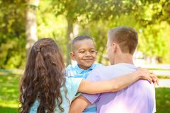 Young family with adopted African American boy. Outdoors Stock Image