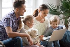 Young family with adopted children using laptop together at home. Smiling parents and son daughter relaxing with computer looking at screen, married couple stock photos