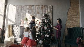 The young family adorns a Christmas tree. Two little sisters dressed in the same clothes run around a Christmas tree. Decorated by their young parents slow stock video