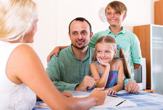 Young family and the agent. Cheerful family and advisor sitting at desk with documents Stock Photos
