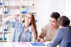 Young family agreeing mortgage contract in the bank for new hous. E Stock Photo