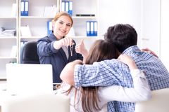 Young family agreeing mortgage contract in the bank for new hous. E Royalty Free Stock Photos