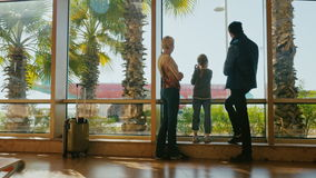 Young family in airport terminal. Stand at the window, look at the planes. Outside, a sunny day, palm trees grow. Arriving at a tropical resort. 4K video stock video
