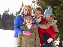Young Family In Alpine Snow Scene. All smiling at camera stock images