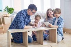 Young Family Assembling Wardrobe stock photo