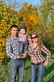Young family in autumn forest Royalty Free Stock Photography