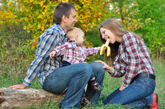 Young family in autumn forest. Boy treats mom banana Royalty Free Stock Photography