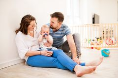 Young family with a baby boy at home, sitting on the floor. Portrait of young family with a baby boy sitting on the floor at home stock photos