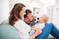 Young family with a baby boy at home, sitting on the sofa. Young family with a baby boy at home sitting on the sofa, playing with a ball stock photos