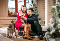 Young family with a baby boy sitting on a sled in Christmas decorations Stock Photo