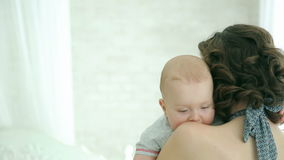 Young family. Baby falls asleep at mum on hands. Dad hugs mom. Happy family. A child 6 months. Bright white room with a bed. Stand by the window stock video footage
