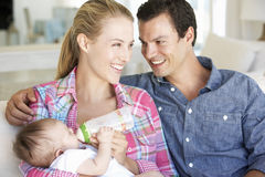Young Family With Baby Feeding On Sofa At Home Royalty Free Stock Images