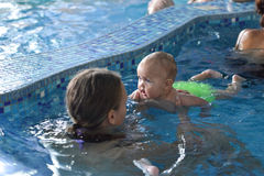 Young family with baby having in the swimming pool. Royalty Free Stock Photo