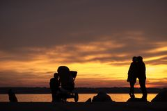 Young family with a baby in a pushchair and kids. Silhouetted against a bright colorful orange sunset over a calm ocean as they stand on the rocks on the Royalty Free Stock Image