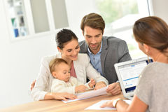 Young family with baby at real-estate agency stock photography