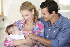 Young Family With Baby Relaxing On Sofa At Home Royalty Free Stock Photos