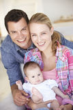 Young Family With Baby Relaxing On Sofa At Home Stock Photos