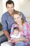 Young Family With Baby Relaxing On Sofa At Home Stock Images