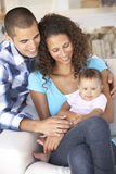 Young Family With Baby Relaxing On Sofa At Home Stock Photography
