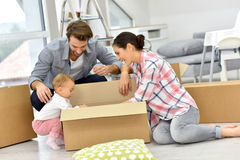 Young family with baby unpacking boxes moving into new house Royalty Free Stock Photos